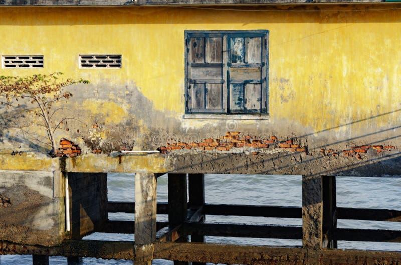 Casa em pernas de pau no mar aberto um quadro de janela com a pintura velha rachada fotos de stock