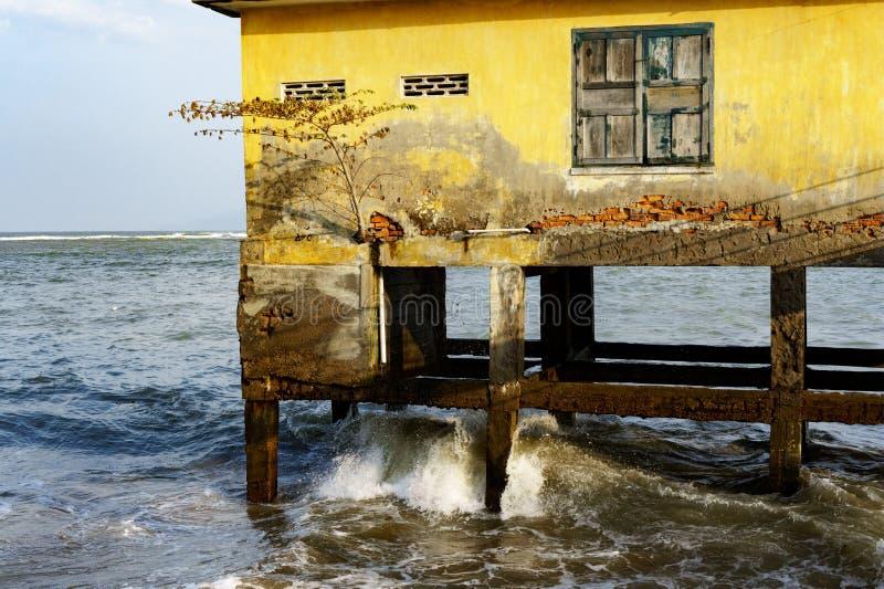 Casa em pernas de pau no mar aberto um quadro de janela com a pintura velha rachada imagem de stock