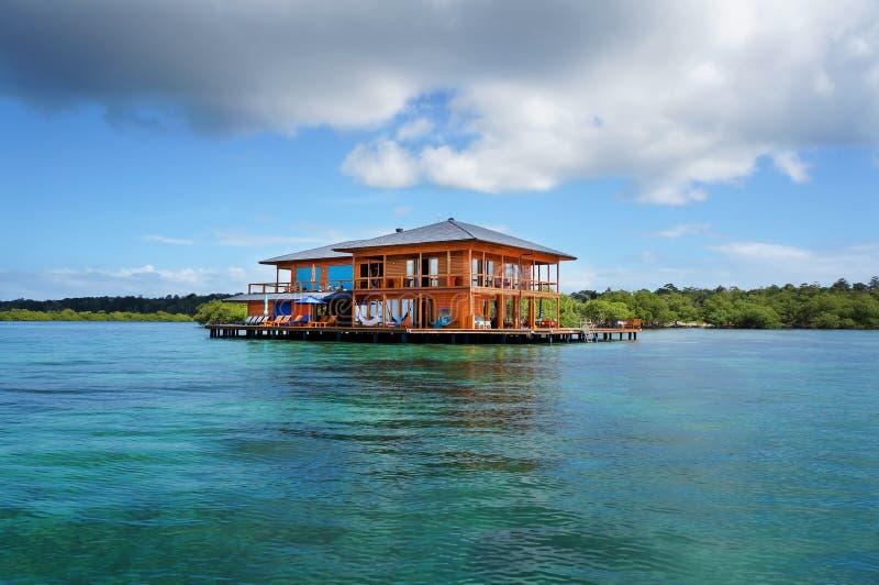 Casa em pernas de pau sobre a água do mar das caraíbas imagem de stock
