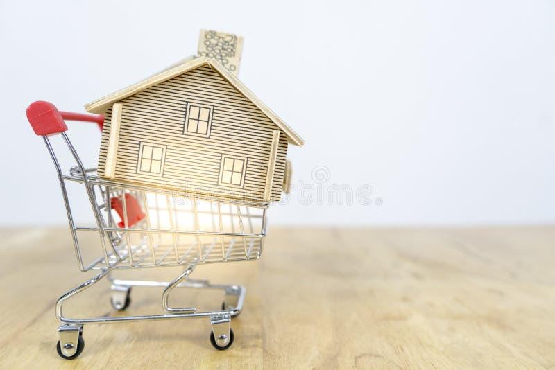 Casa en carro de la compra, cómo hacer un dueño de la casa, conceptos sobre compras en línea, casa de la compra y de la venta imagen de archivo libre de regalías
