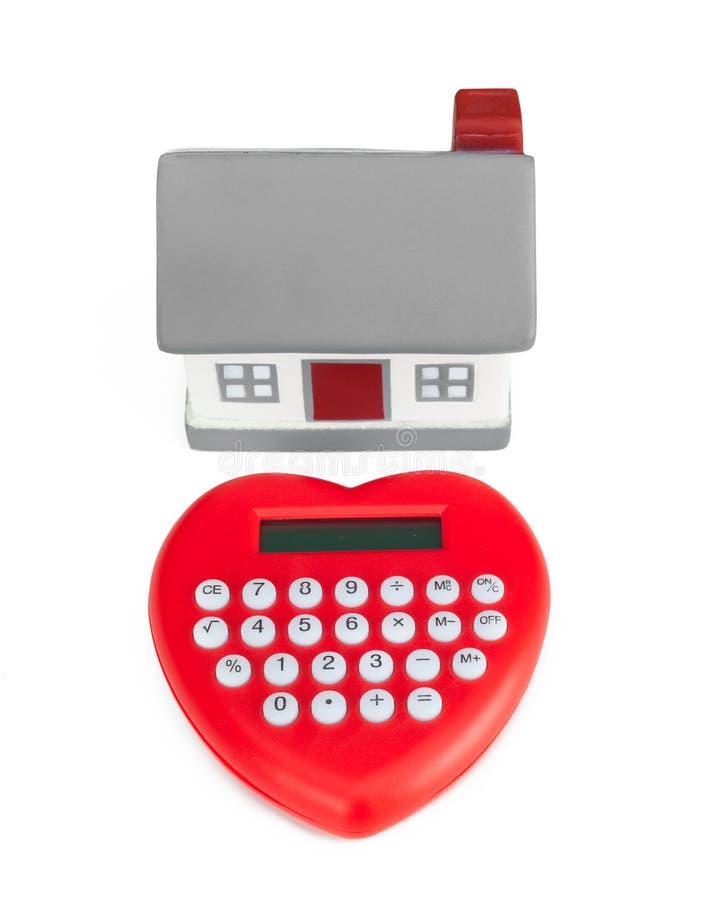Casa en forma de corazón y miniatura de la calculadora fotos de archivo