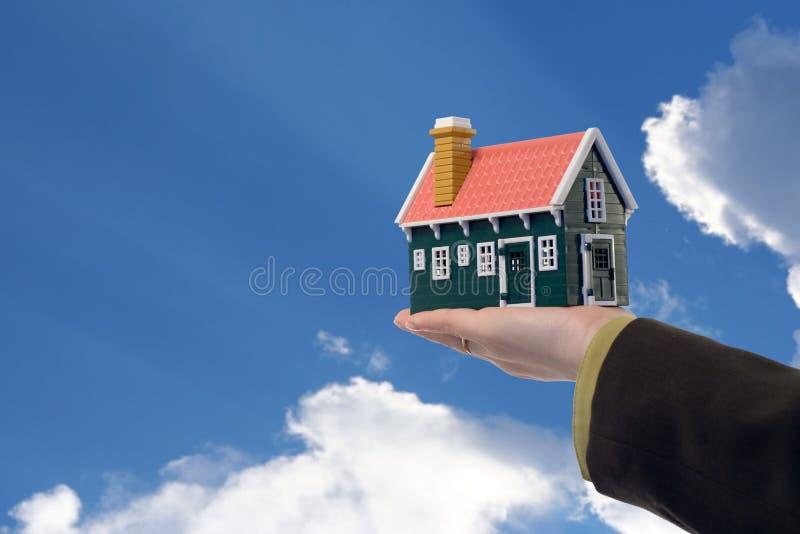 Casa en mano y cielo de la mujer foto de archivo