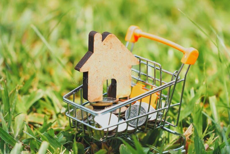 Casa en mini carro de la compra con la pila de dinero de las monedas para la inversión residencial imágenes de archivo libres de regalías