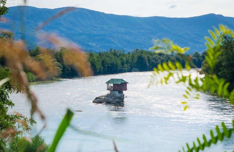 Casa en roca en el río imagenes de archivo