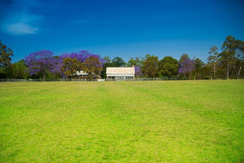 Casa en una pradera con la cerca y los árboles blancos fotos de archivo