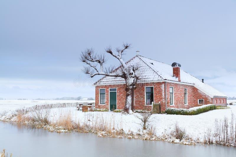 Casa encantadora en nieve del invierno por el río imagen de archivo