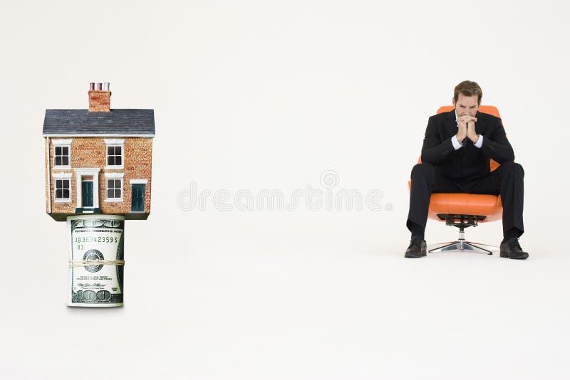 Casa encima del rollo de cuentas con el hombre de negocios pensativo en la silla que representa las propiedades inmobiliarias cost imagenes de archivo