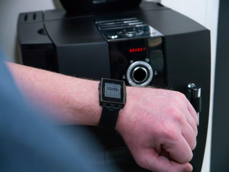 Casa esperta: Equipe a verificação da máquina do café com seu relógio esperto fotografia de stock
