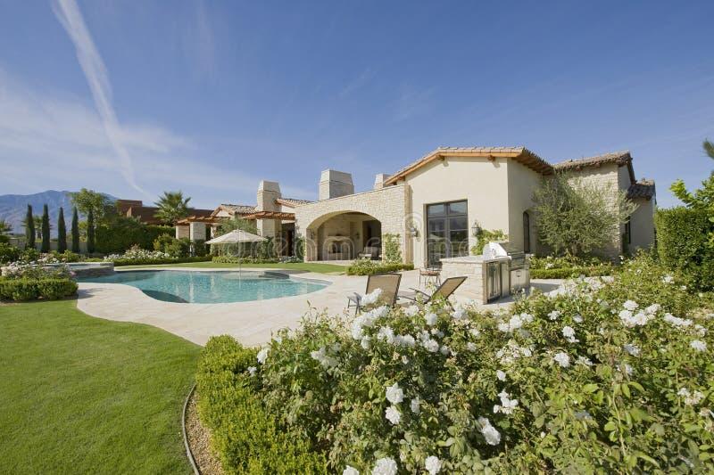 Casa exterior com piscina e jardim imagens de stock