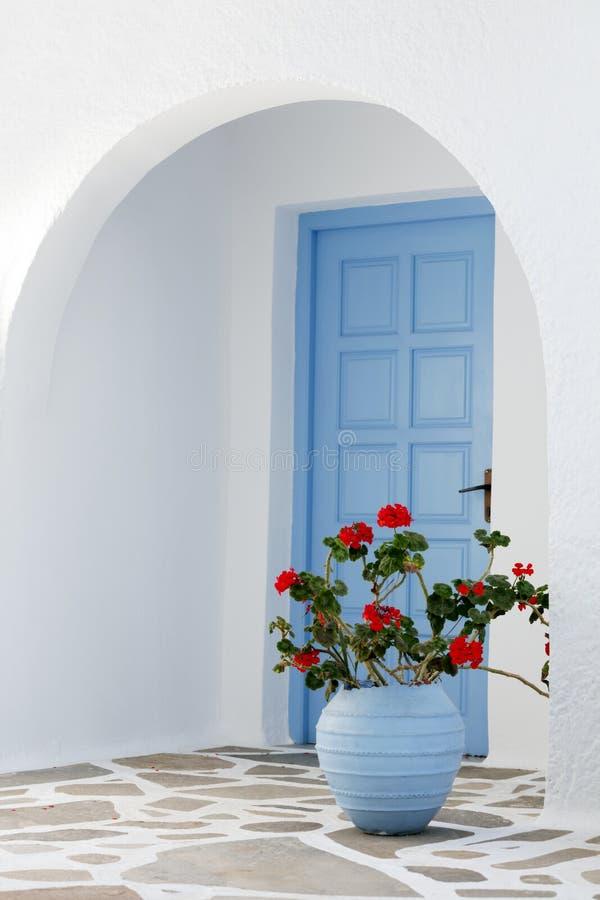 Casa exterior com porta e as flores azuis em Grécia foto de stock royalty free