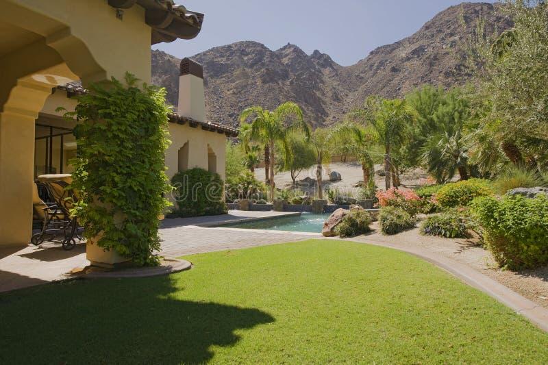 Casa exterior con la piscina en jardín foto de archivo