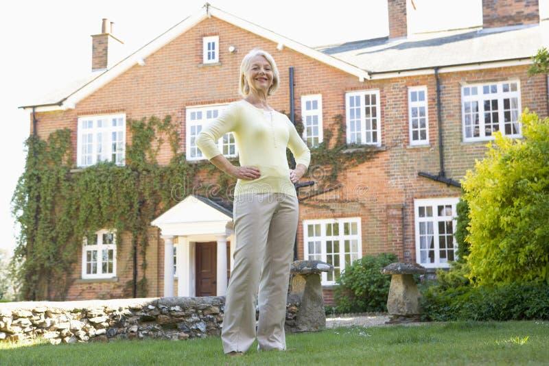 Casa exterior ereta da mulher sênior fotos de stock royalty free