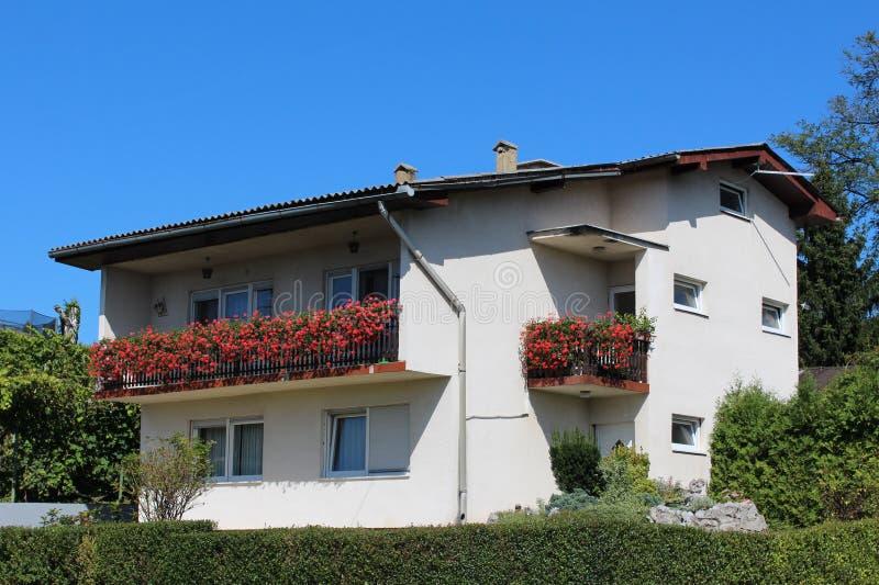 Casa familiar de color blanco suburbano con un gran balcón frontal lleno de flores de color rojo brillante rodeada de una cobertu fotos de archivo