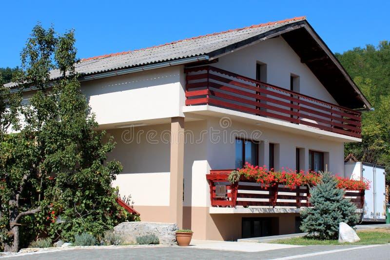 Casa familiar de estilo suburbano reformada con dos largos balcones frontales llenos de flores rojas junto a la carretera pavimen fotos de archivo