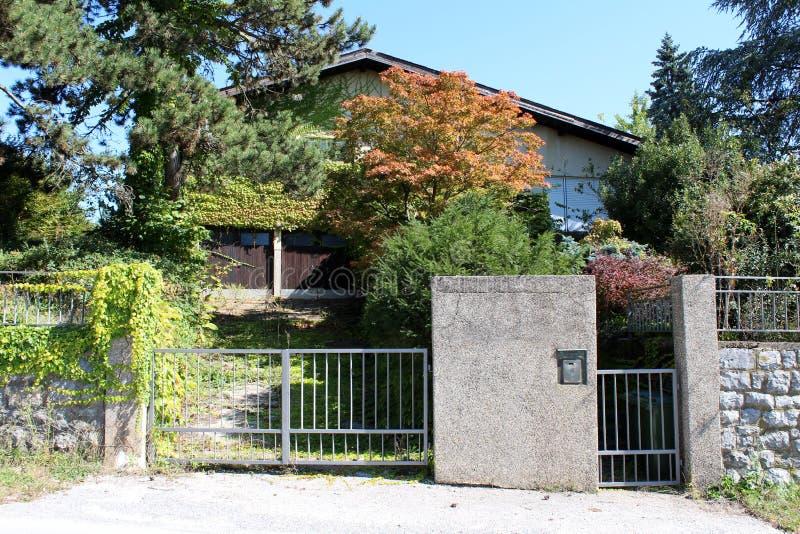 Casa familiar suburbana con una carretera sobrepoblada que conduce a dos entradas de garaje escondidas de calles públicas con pla imagen de archivo