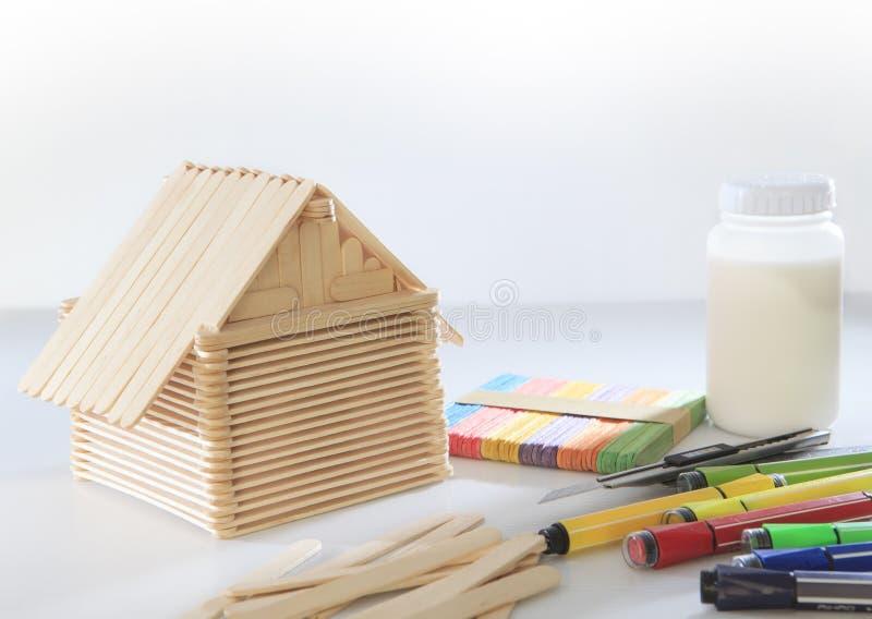 Casa fatta dal legno del ghiacciolo su uso bianco del fondo per childre fotografia stock