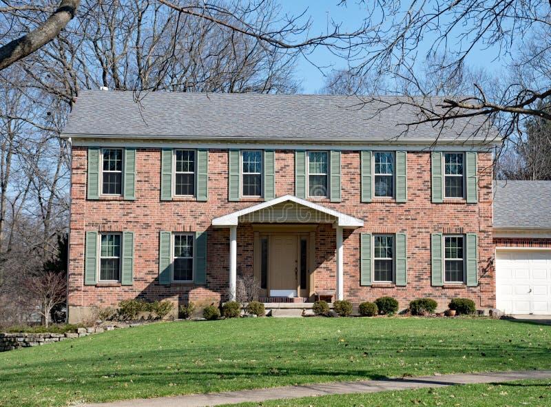 Casa federal del estilo del ladrillo rojo con Teal Shutters foto de archivo