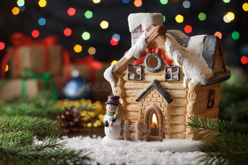 A casa feericamente do cartão de Natal com pinho ramifica, presentes, fundo colorido das luzes fotografia de stock royalty free