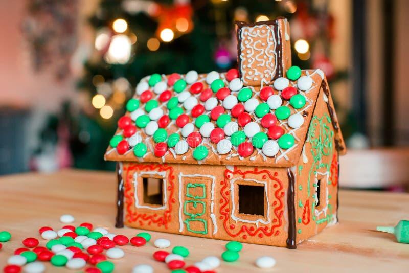 Casa feericamente do pão-de-espécie em um fundo da árvore de Natal brilhante com festão imagens de stock royalty free