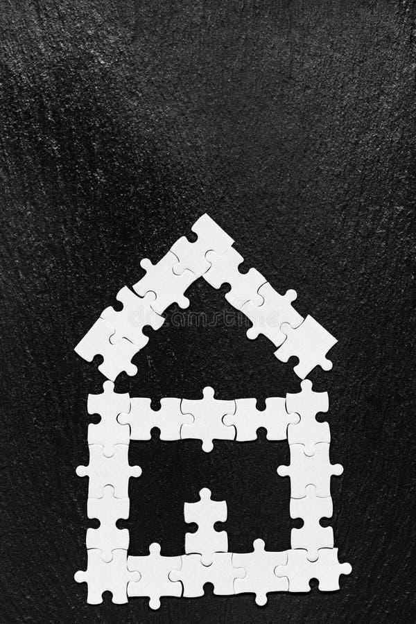 Casa feita dos enigmas Partes brancas do enigma moderno da casa para o projeto de conceito Casa da serra de vaivém, construção, e foto de stock