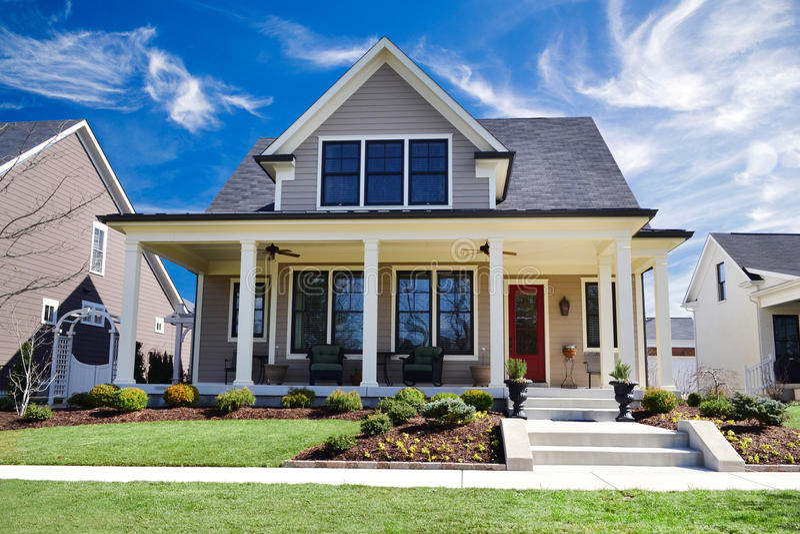 Casa feita sob encomenda brandnew do estilo tradicional com grande Front Porch e ajardinar bonito fotos de stock royalty free