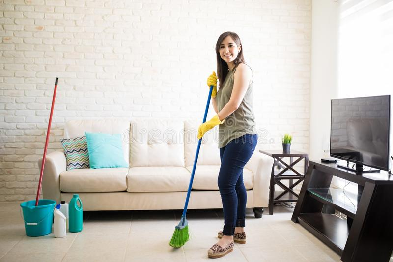 Casa feliz de la limpieza de la criada cerca de la televisión foto de archivo