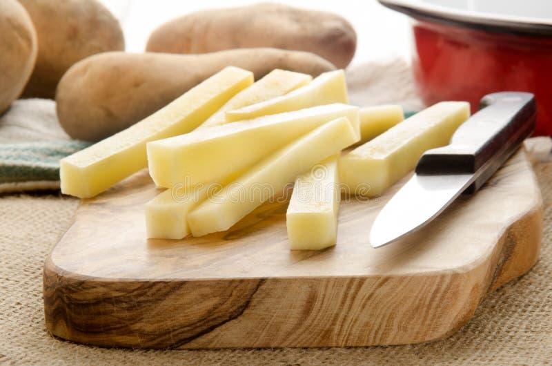 A casa fez batatas fritas na placa de madeira imagem de stock