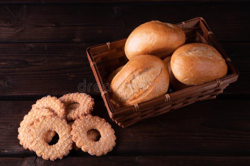 A casa fez cookies e bolos na cesta em um fundo de madeira, baixa chave do pão imagem de stock royalty free