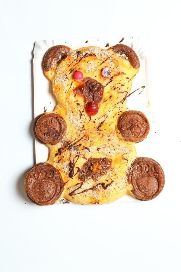 A casa fez o bolo na forma do urso branco com olhos dos doces e as patas marrons fotos de stock