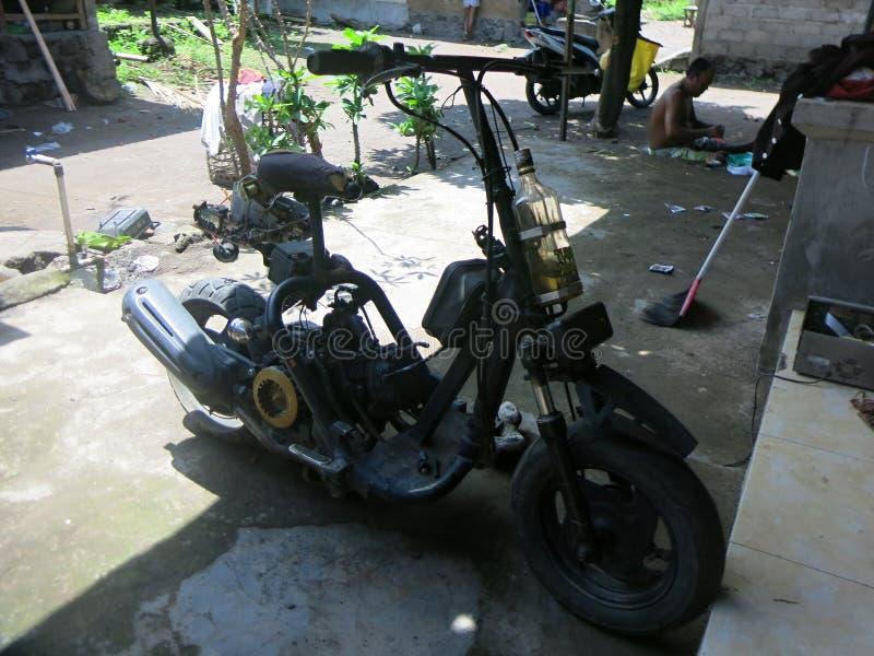 A casa fez o 'trotinette' É muito comum em Indonésia encontrar bicicletas e 'trotinette's similares na estrada Polícia local para imagem de stock
