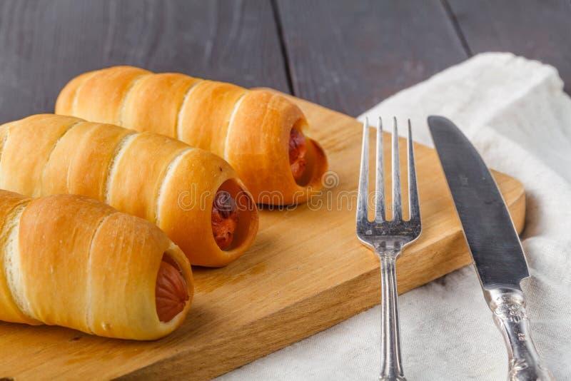 A casa fez porcos em uma cobertura As salsichas rolaram na massa do croissant, cozida imagens de stock