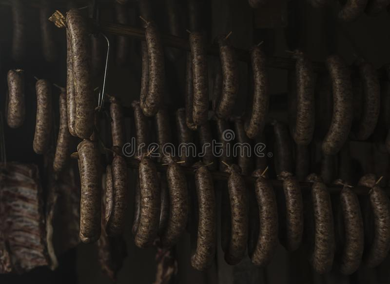 A casa fez salsichas está pendurando em uma sala fumado foto de stock royalty free