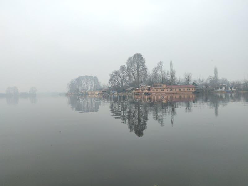 Casa flutuante, árvores e sua reflexão no lago Nageen, srinagar foto de stock