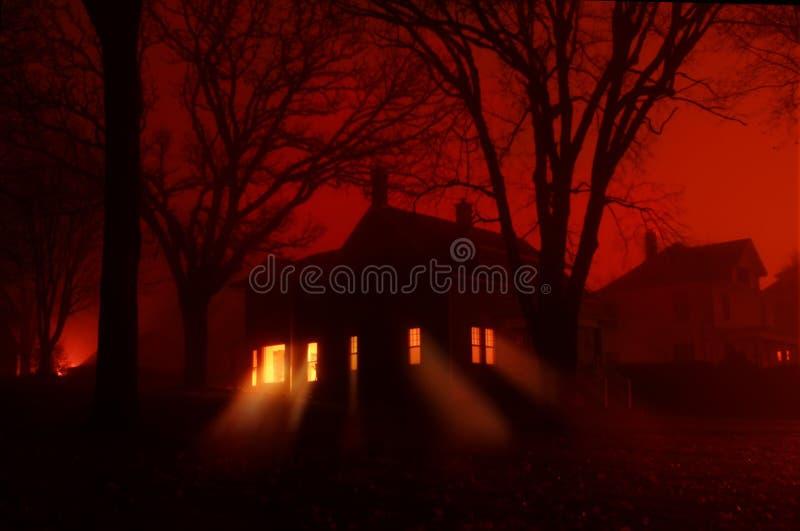 Casa frecuentada en niebla roja foto de archivo