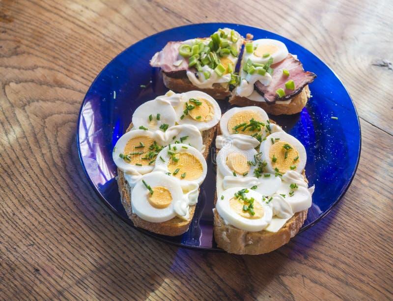 A casa fresca ascendente próxima fez o sanduíche do pão de centeio com fatias do ovo, bacon do presunto, cebolinho e maionese na  imagens de stock royalty free
