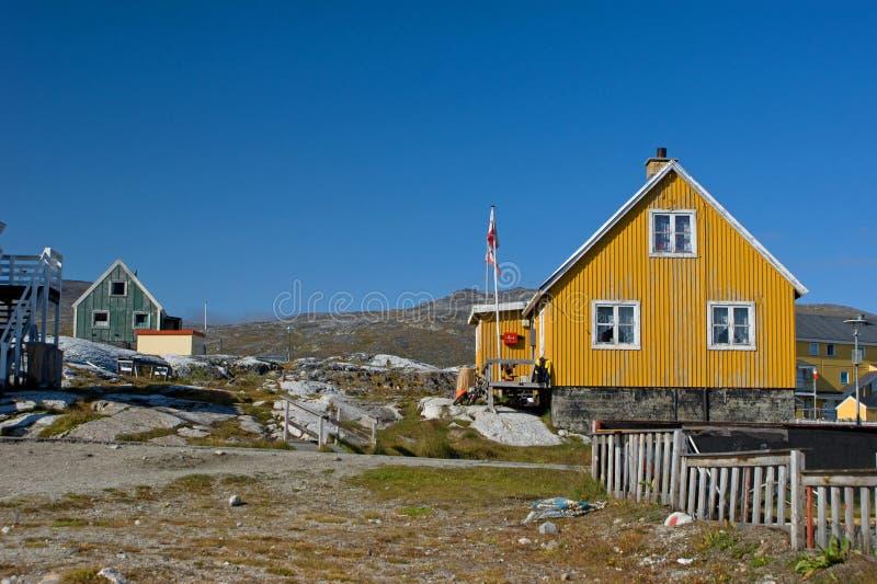 Casa gialla in Groenlandia con la bandierina e la rete fissa immagini stock