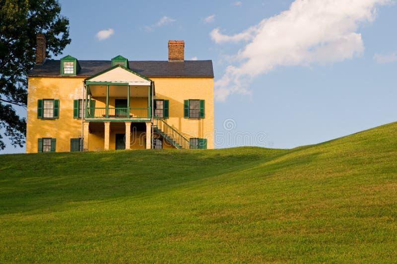 Casa gialla sulla collina erbosa immagine stock