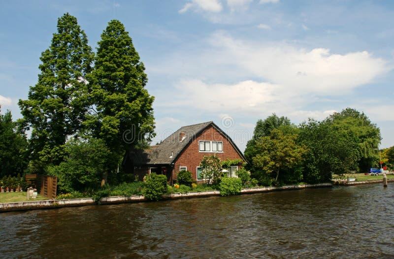 Casa, giardino, canale ed alberi olandesi fotografia stock libera da diritti