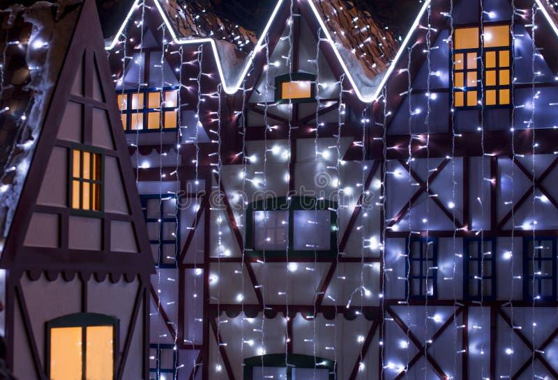 Casa grande hermosa adornada con las luces de la Navidad Windows grande con el árbol de navidad ilustración del vector
