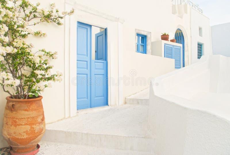 Casa grega branca com o potenciômetro azul da porta e de flor fotografia de stock