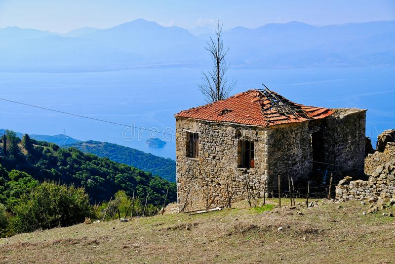 Casa griega vieja de la piedra del pueblo de montaña que pasa por alto el golfo de Corinto imagen de archivo libre de regalías
