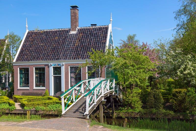 Casa holandesa verde tradicional con poco puente de madera contra el cielo azul en el pueblo de Zaanse Schans, Países Bajos Turis imagen de archivo libre de regalías