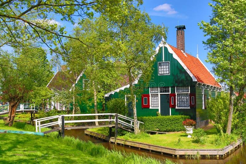 Casa holandesa verde tradicional con poco puente de madera contra el cielo azul en el pueblo de Zaanse Schans, Países Bajos Turis fotos de archivo libres de regalías
