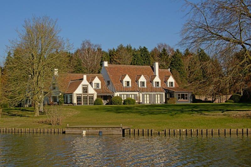 Casa idilliaca lungo il fiume Lys in Fiandre, Belgio fotografia stock