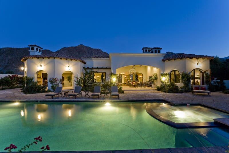 Casa iluminada con la piscina en la oscuridad imagenes de archivo