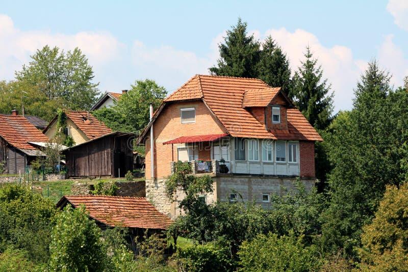Casa inacabada de la familia del ladrillo rojo al lado de la vertiente de madera del utensilio de jardinería rodeada con casas má imágenes de archivo libres de regalías