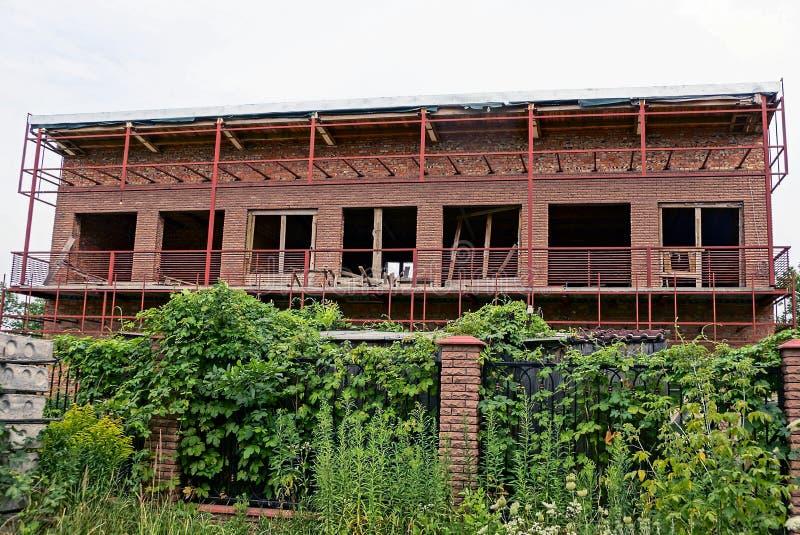 Casa inacabada grande detrás de la cerca con la vegetación verde imagen de archivo