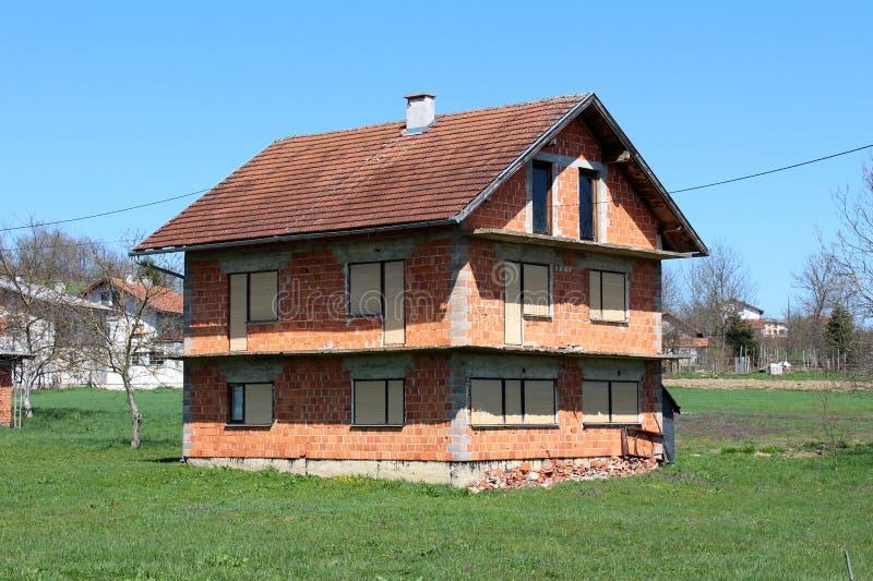 Casa inacabado abandonada do tijolo vermelho com as cortinas de janela completamente fechados cercadas com as casas sem cortes da imagem de stock