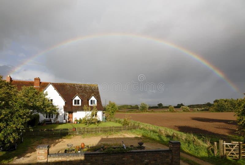 Casa inglese con l'arcobaleno in campagna immagini stock
