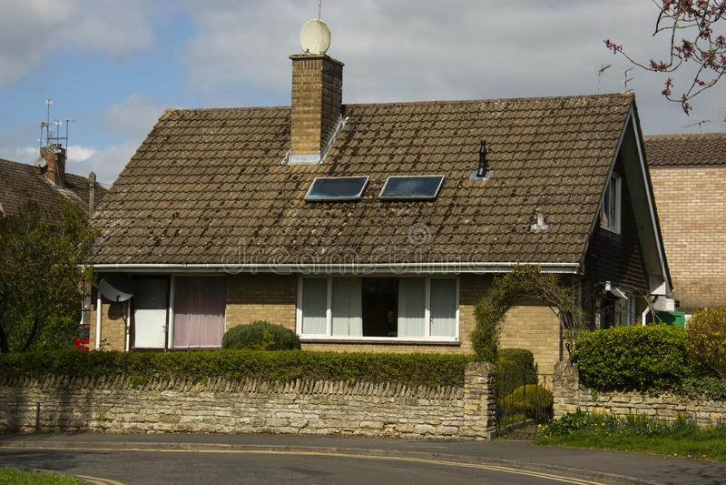 Casa inglese tradizionale e tipycal Casa della pietra del mattone Vista della via Il tempo di primavera… è aumentato foglie, sfon fotografia stock libera da diritti